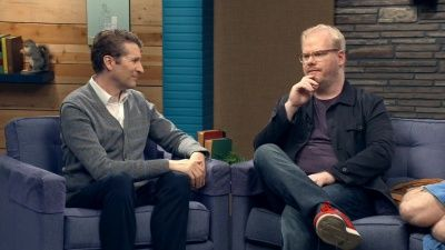 Jim Gaffigan Wears a Blue Jacket & Plum T-Shirt